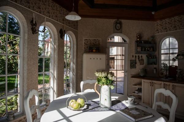 10-cozy-beige-and-turquoise-garden-gazebo-interior-design-summer-kitchen-dining-room-set-bay-windows-mosaic-tiles-retro-lamps-garden-view-vintage-tabelware-decor-brass-decoupage-furniture-shelves-smeg-refrigerator