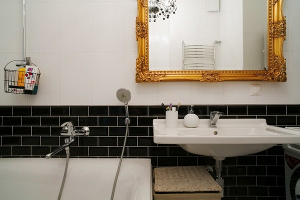 23-minimalist-interior-style-bathroom-white-walls-vitra-sanitary-black-brick-wall-tiles-golden-framed-mirror