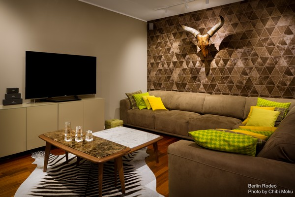 5-bachelor-pad-interior-modern-style-living-room-unusual-geometrical-3D-wall-zebra-skin-on-the-floor-head-with-horns-on-the-wall-marble-table-top-beige-sofa-green-couch-pillows