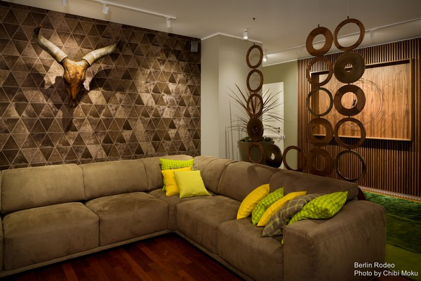 6-bachelor-pad-interior-modern-style-living-room-unusual-geometrical-3D-wall-head-with-horns-on-the-wall-beige-sofa-green-couch-pillows-track-lights