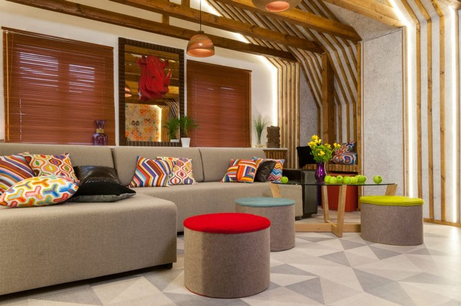 1-bright-colorful-attic-floor-interior-design-living-room-corkwood-floor-wall-wooden-planks-wall-decor-recessed-lighting-LED-bands-big-gray-corner-sofa-glass-table-rhino-head-ottomans