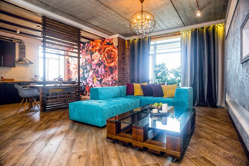 1-mixed-style-brutal-loft-pop-art-eco-style-apartment-interior-design-ceiling-faux-concrete-walls-open-wiring-wooden-planks-open-plan-living-room-floral-wall-mural-bright-blue-velvet-sofa-big-wheeled-coffee-table
