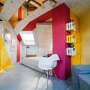 2-ultra-bright-attic-interior-design-diagonal-funriture-arrangement-plastic-mirror-ceiling-panels-brick-tiles-gray-yellow-fuchsia-pink-accents-load-bearing-column-door-painting