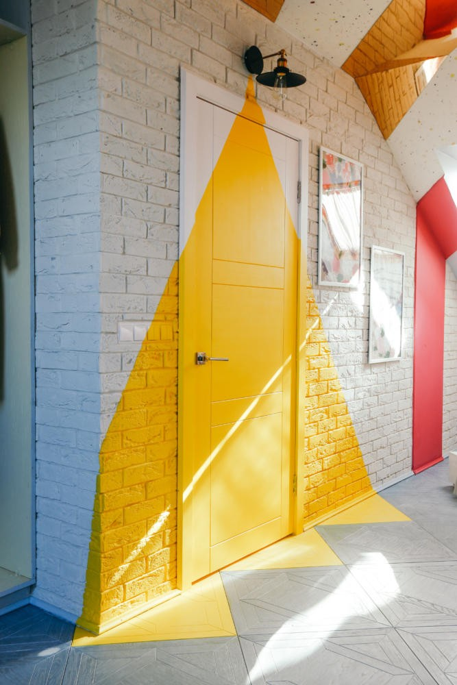 5-ultra-bright-attic-interior-design-diagonal-funriture-arrangement-unusual-highlighting-of door-area-yellow-painting-faux-brick-tiles-mirror-ceiling-panels