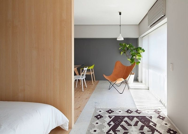 6-2-wooden-partition-between-bedroom-and-living-room-panoramic-windows-black-and-white-rug-orange-folding-arm-chair-L-shaped-layout-without-doors