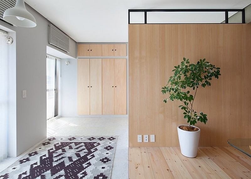 6-totally-wooden-apartment-with-unusual-L-shaped-layout-open-concept-wooden-floor-walls-furniture-concrete-ceiling-black-and-white-rug-panoramic-window-big-potted-indoor-plant-without-doors