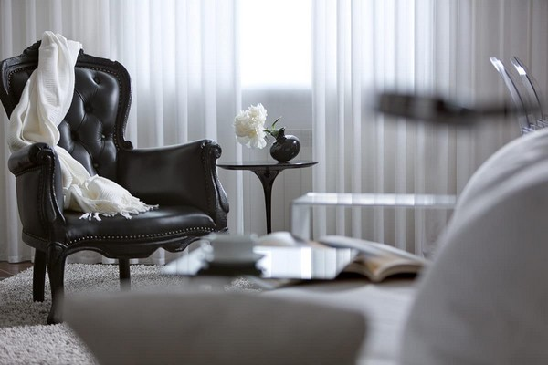9-cozy-elegant-neo-classical-modern-black-and-white-interior-design-open-concept-living-room-white-sofa-with-mirrored-arm-rest-Flexform-black-leather-arm-chair-Mui-Olivar-coffee-table