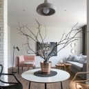 0-minimalist-style-studio-apartment-interior-design-open-concept-white-walls-dining-living-room-clincker-bricks-Philippe-Starck-chairs-copper-black-round-table-tree-branch