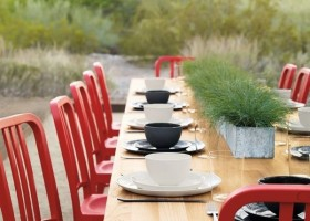 0-red-dining-chairs-big-wooden-table-in-exterior-design-outdoors-party-setting-black-and-white-tableware