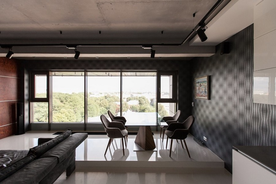 1-2-bachelor's-loft-style-open-concept-living-dining-room-interior-design-panoramic-window-gray-concrete-ceiling-self-leveling-polymeric-floor-blue-wallpaper-track-lights-podim-table-chairs-bubinga-wooden-wall