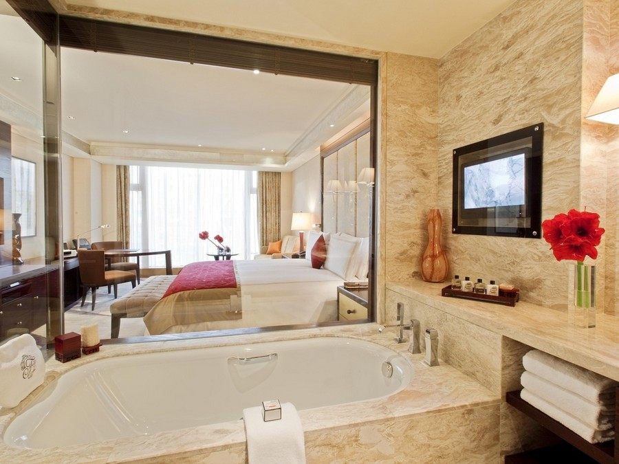 1-TV-set-in-bathroom-interior-design-beige-walls-glass-wall-to-bedroom