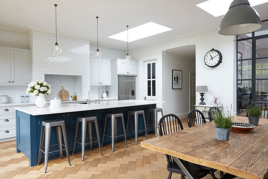 1-white-brick-wall-tiles-kitchen-interior-design-island-blue-cabinets-pendant-lamps-parquet-floor-boards-wooden-dining-table