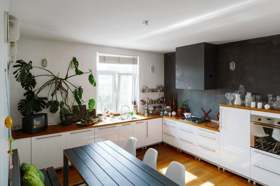 3-eclectic-style-kitchen-interior-design-white-walls-cheese-plant-sink-near-window-no-upper-cabinets-white-base-IKEA-set-wooden-worktop-black-backsplash-wall-cooker-hood-concealed-shelves-floor-dining-table