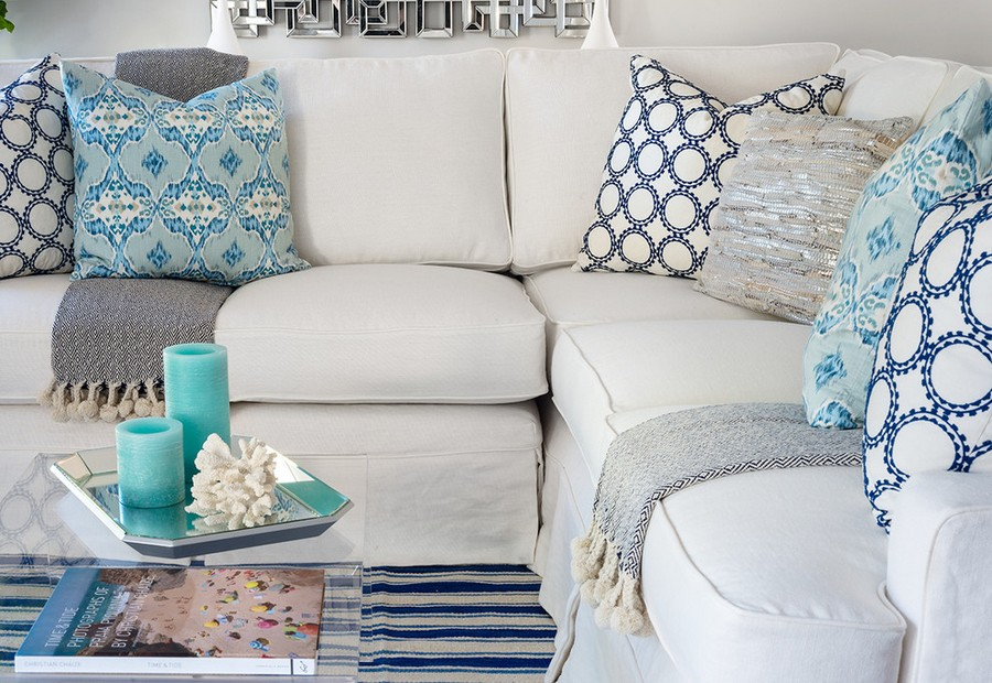 3-soft-upholstered-beige-sofa-couch-cushions-decorative-blue-and-turquoise-pillows-glass-coffee-table-tray-cups-book-blanket