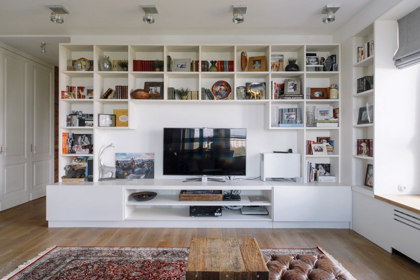 4-1-minimalist-style-white-walls-and-gray-apartment-interior-design-open-concept-living-room-big-shelving-unit-carpet-roman-blinds-TV-set-leather-ottoman-vintage-wooden-coffee-table