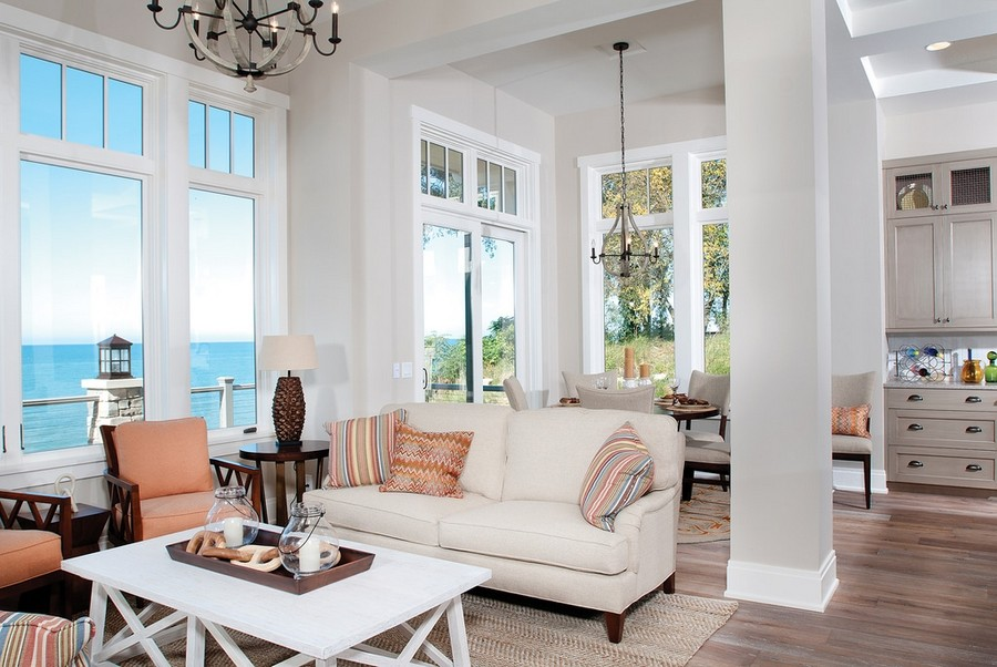 6-2-open-concept-kitchen-dining-living-room-interior-design-traditional-style-neutral-colors-beige-brown-white-gray-panoramic-windows-ocean-sea-view-sofas-arm-chairs-coffee-table-stripy-pillows-load-bearing-columns