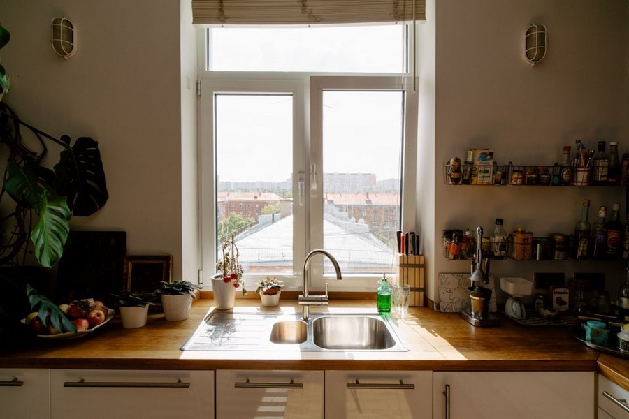 6-eclectic-style-kitchen-interior-design-white-walls-cheese-plant-sink-near-window-no-upper-cabinets-white-base-IKEA-set-wooden-worktop-bathroom-shelves