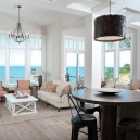 6-open-concept-kitchen-island-dining-living-room-interior-design-in-traditional-style-neutral-colors-beige-brown-white-gray-panoramic-windows-ocean-sea-view-sofas-arm-chairs-coffee-table-load-bearing-columns