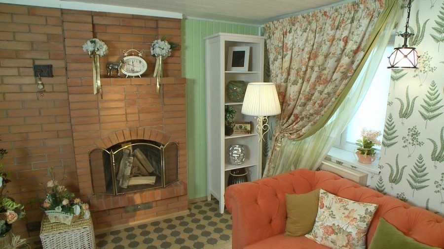 7-1-Provence-style-living-room-interior-design-green-mint-and-coral-colors-brick-fireplace-floral-fern-wallpaper-curtains-drapery-white-shelf-unit-sofa