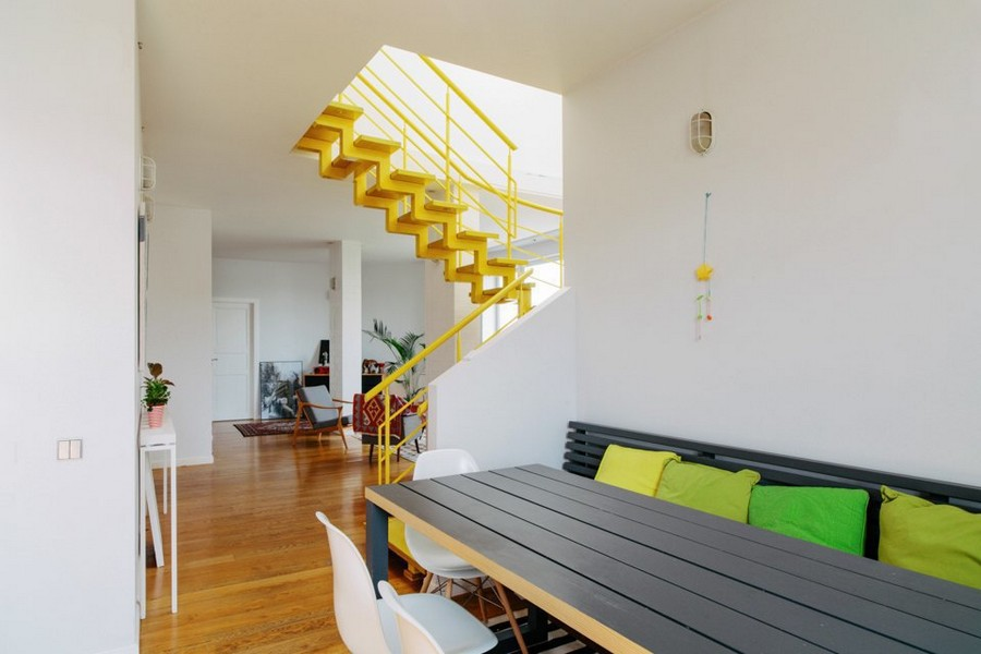 7-eclectic-style-open-concept-lounge-kitchen-interior-design-white-walls-wooden-floor-dining-table-bench-decorative-pillows-yellow-staircase-corridor