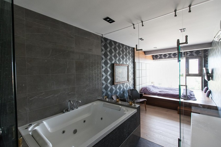 8-1-bachelor's-loft-style-bedroom-interior-design-panoramic-window-blue-wallpaper-podium-bed-tall-upholstered-headboard-glass-wall-to-bathroom-bathtub-gray-wall