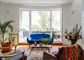 8-eclectic-style-living-room-interior-design-white-walls-bright-accents-many-potted-indoor-plants-lounge-retro-blue-sofa-ethnical-arm-chair-panoramic-window-baclony-exit-Indian-coffee-table-carpet