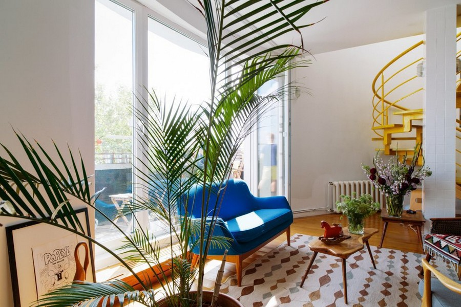 9-eclectic-style-living-room-interior-design-white-walls-bright-accents-many-potted-indoor-plants-lounge-retro-blue-sofa-ethnical-arm-chair-panoramic-window-baclony-exit-Indian-coffee-table-carpet