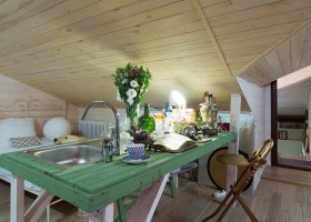 0-eclectic-style-bedroom-interior-design-in-the-loft-attic-sloped-wooden-ceiling-metal-bed-framework-small-kitchen-island-with-exposed-pipes-green-wooden-countertop-sink-samovar-bar-table-stools