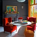 00-flame-red-color-by-Pantone-2017-in-interior-design-living-room-dark-gray-walls-arm-chairs-sofa-whie-floor-fireplace