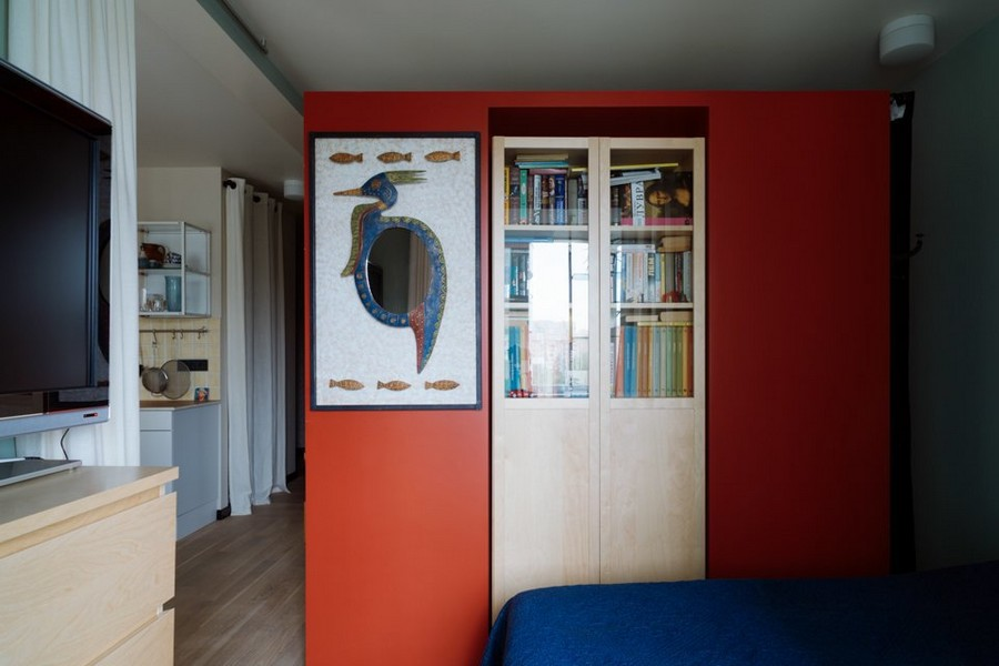 1-3-bachelor's-interior-design-open-concept-room-light-blue-walls-yellow-red-wall-accents-curtains-bookstand-IKEA-mirror-TV-set-kitchen-bedroom-plasterboard-structure