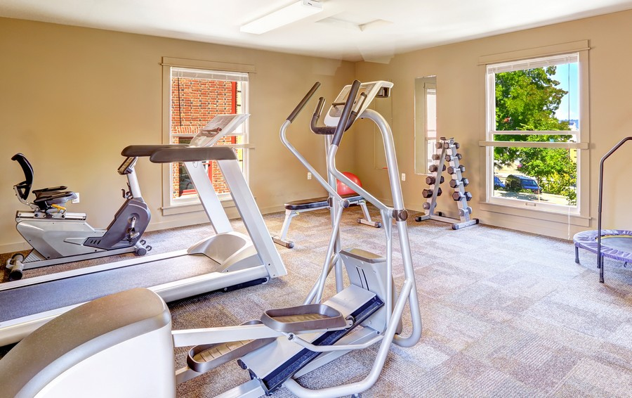 1-home-gym-interior-design-light-neutral-colors-windows-fitness-exercise-equipment-beige-walls-racetrack