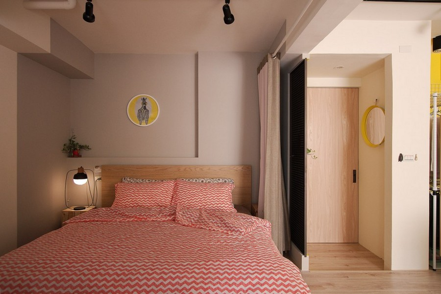 1-studio-apartment-design-light-floating-wood-floor-track-lights-beige-walls-red-and-white-bed-linen-curtained-bed-entrance-door-zoning