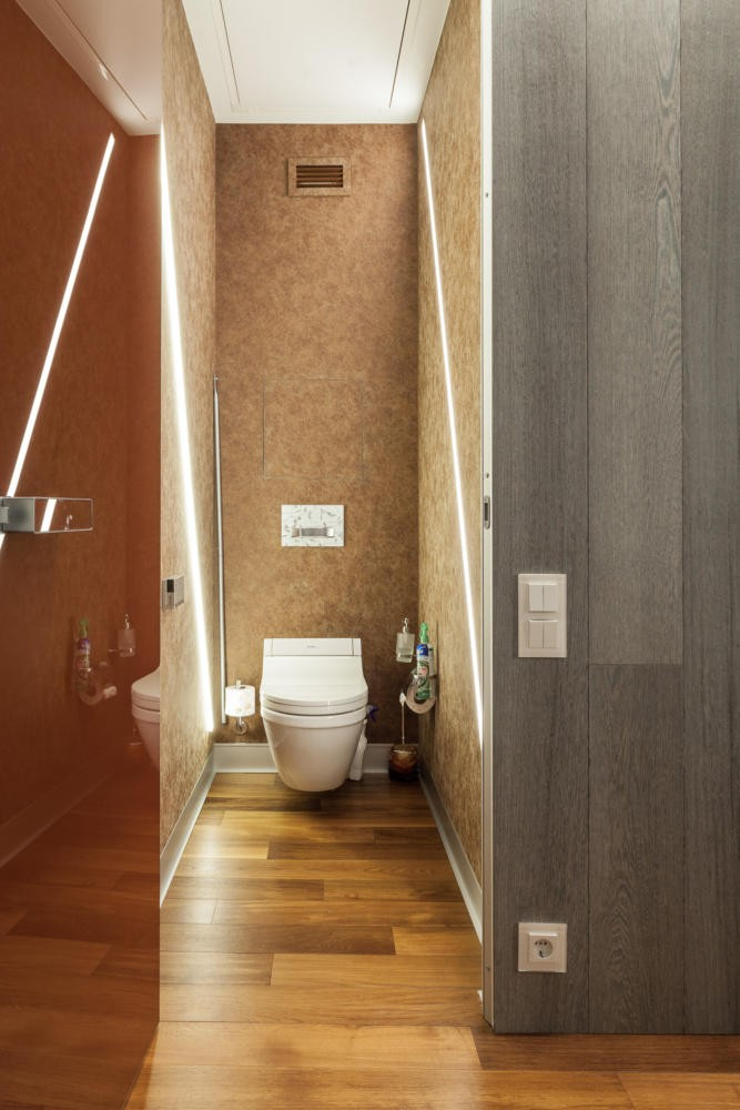 11-contemporary-style-toilet-interior-design-LED-panels-lights-suspended-bowl-gray-parquet-wall-teak-parquet-floor-brown-glass-door-attic-door-in-the-ceiling-garret
