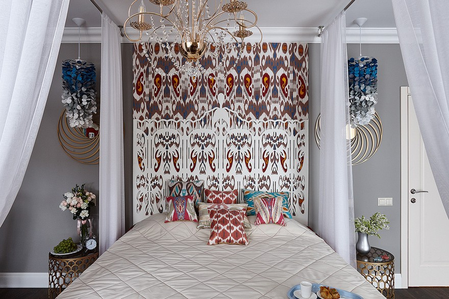2-1-contemporary-style-bedroom-interior-design-with-oriental-Central-Asian-Uzbek-motifs-canopy-bed-ikat-pattern-wallpaper-white-red-gray-blue-accents-pomegranate-carved-headboard-felt-lamp-ombre-effect-throw-pillows