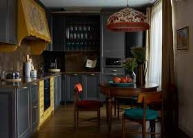 2-1-neo-classical-style-kitchen-dining-room-interior-with-ethnic-motifs-Central-Asian-Uzbek-Portuguese-dark-blue-cabinets-red-chairs-yellow-brass-accents-wooden-cooker-hood-marble-countertop-backsplash