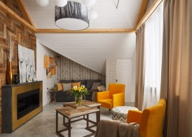 2-contemporary-style-attic-interior-metal-and-concrete-bio-fireplace-sloped-ceiling-white-walls-wooden-wall-decor-yellow-arm-chairs-living-room-coffee-table-sofa-naturalistic-wallpaper-corkwood-floor-faux-beams