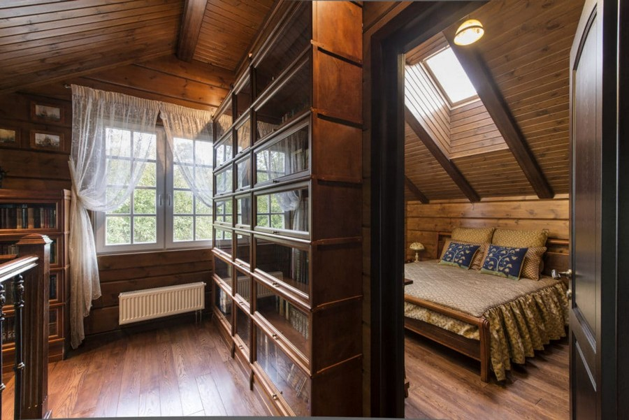 3-1-log-timber-wooden-house-bedroom-interior-design-brown-walls-sloped-ceiling-skylights-sheer-curtains-draped-bedspread-beige-blue-throw-pillows-bed-cover-bedspread-with-cord-trim
