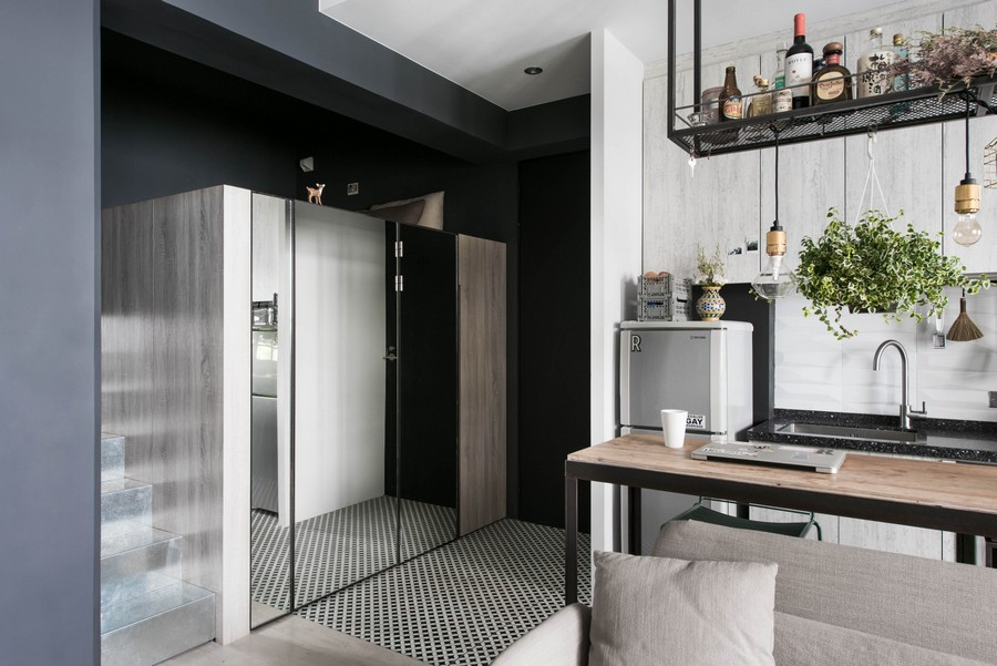 3-2-tiny-small-single-woman's-studio-apartment-Taiwan-gray-walls-floor-black-interior-design-accents-light-wood-graphite-loft-bed-with-storage-zone-underneath-mirrored-wardrobe-doors-kitchen-cabinets