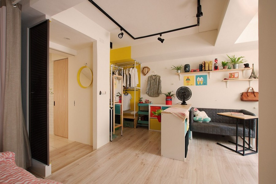 3-studio-apartment-design-light-floating-wood-floor-track-lights-beige-walls-red-blue-yellow-accents-shelving-unit-curtained-bed