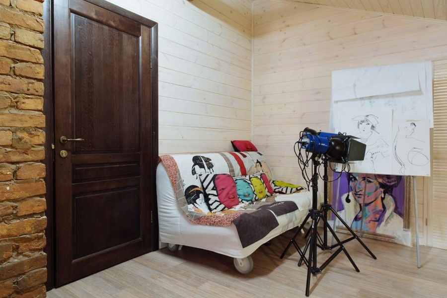 4-2-eclectic-style-interior-wooden-walls-old-brick-masonry-dark-wood-door-small-wheeled-sofa-cameras-paintings-Diana-Spencer