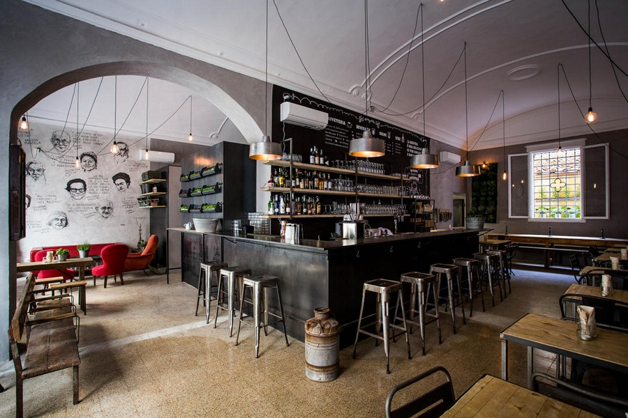 5-1-Gesto-restaurant-cafe-bar-in-Milan-Italy-loft-style-interior-design-exposed-wires-lamps-metal-stools-chairs-red-arm-chairs-sofa-bar-gray-walls