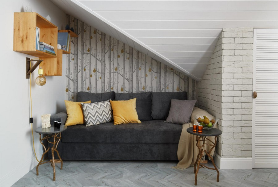 5-1-contemporary-style-attic-interior-sloped-ceiling-white-walls-wooden-shelves-yellow-pillows-gray-sofa-living-room-coffee-tables-forged-naturalistic-wallpaper-corkwood-floor-brass-sconce-lamp-storage-area
