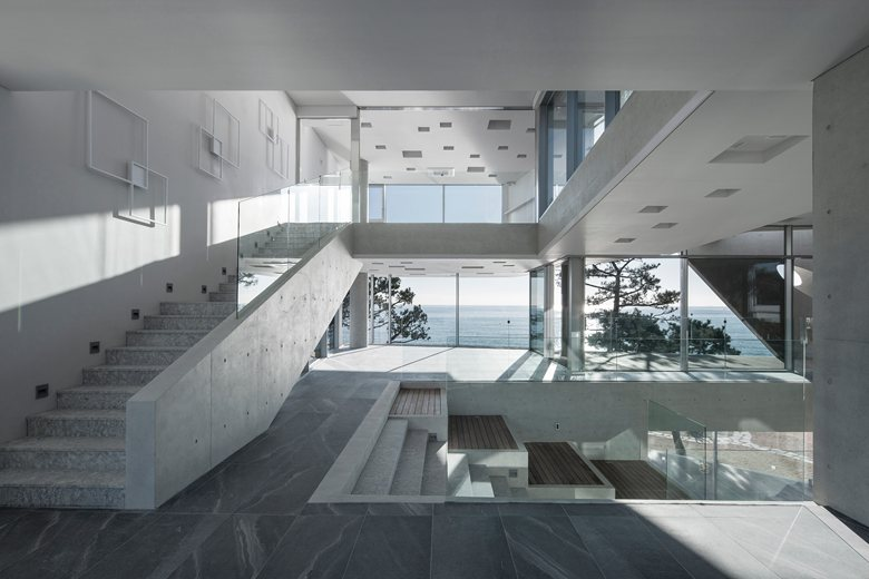 6-coastal-seaside-cafe-in-South-Korea-sea-view-restaurant-minimalist-concrete-building-interior-design-white-sloped-ceiling-panoramic-windows-glass-staircase-railings
