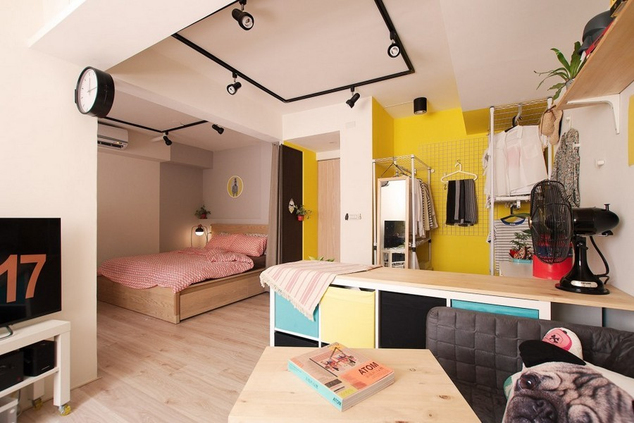 7-1-studio-apartment-design-light-floating-wood-floor-track-lights-beige-walls-red-blue-yellow-accents-shelving-unit