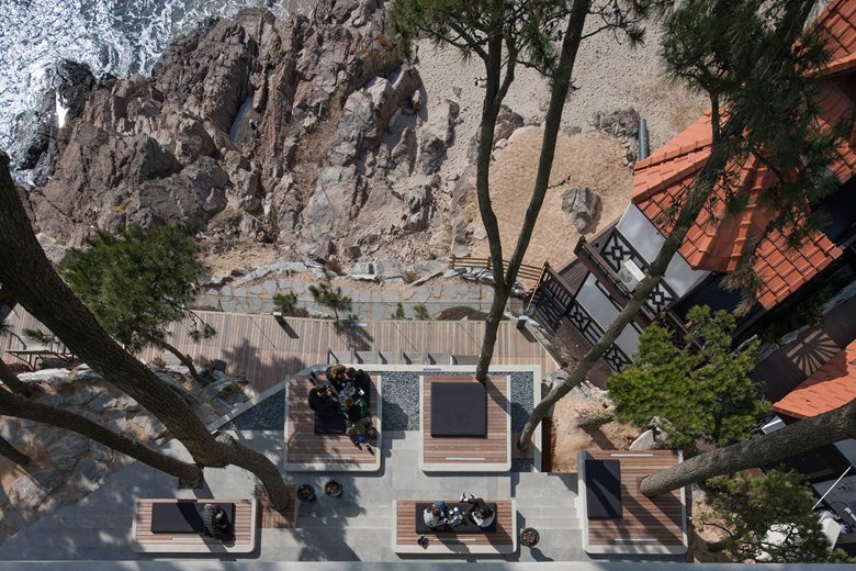 7-coastal-seaside-cafe-in-South-Korea-sea-view-restaurant-tall-conifers-trees-rocky-beach-open-terrace-picnic-spots-benches-mats-exterior-design