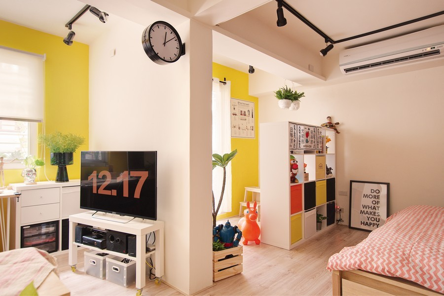 8-1-studio-apartment-design-light-floating-wood-floor-track-lights-beige-walls-red-blue-yellow-accents-shelving-unit-TV-set-clock
