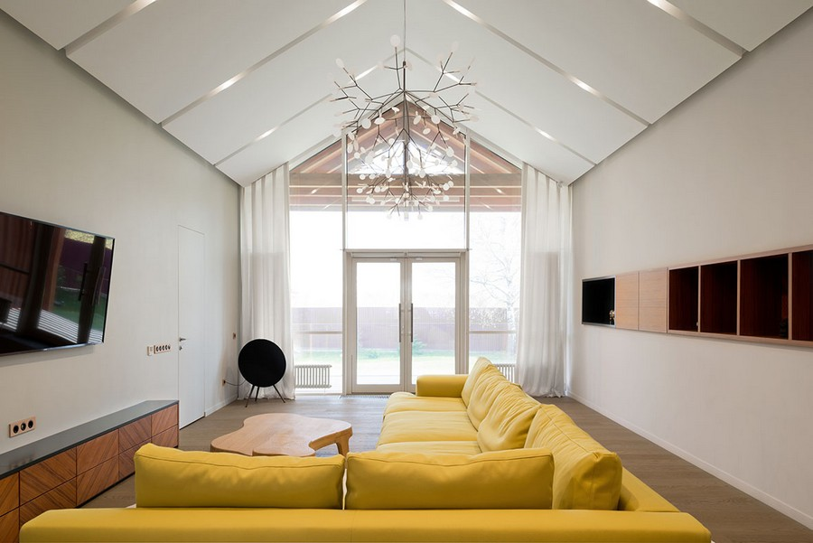 9-2-open-concept-living-room-kitchen-dining-zone-interior-design-in-contemporary-style-white-walls-minimalism-spacious-big-yellow-corner-sofa-panoramic-window-timber-house-wooden-cabinets-chandelier