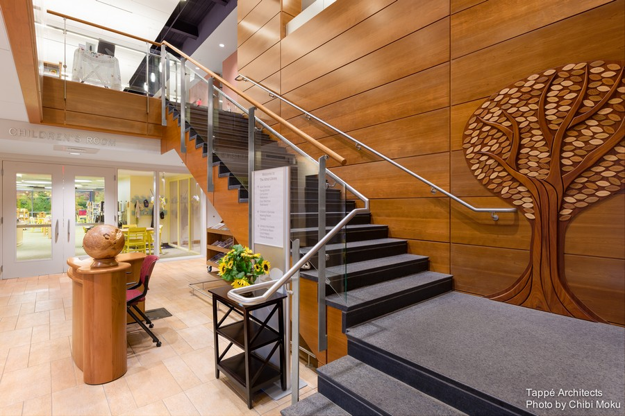 Tappe-Architects-small-town-LEED-platinum-Athol-Public-lbrary-Massachusetts-USA-interior-design-first-floor-reception-desk-wooden-wall-decor-tree-cherry-wood-staircase-glass