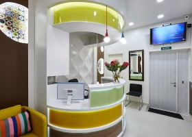 0-bright-multicolored-doctor's-dentist's-office-dental-clinic-contemporary-interior-design-Paul-Smith-style-stripes-creative-reception-desk-3D-wall-faux-windows-LED-lights-white-brown-waiting-area-TV-set-bulbs