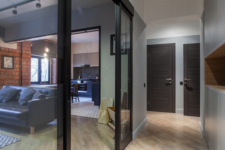 1-1-bachelor's-pad-interior-design-loft-style-brutal-open-concept-living-room-kitchen-corridor-glass-sliding-door-dark-doors-light-laminate-floor-gray-walls